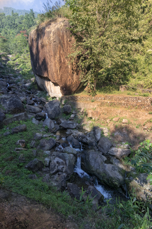 Vertical image of Apple stone - a big apple shaped rock beside a river, beautiful nature stock image of Jhalong, Dooars, North Bengal - West Bengal , India