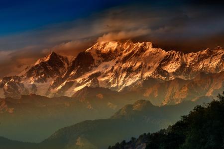 Orange sunset on Chaukhamba , a mountain massif in the Gangotri Group of the Garhwal Himalaya. It lies at the head of the Gangotri Glacier at Uttarakhand, India.