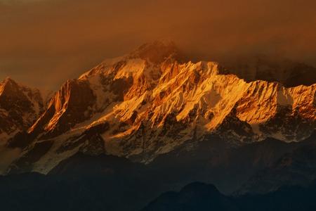 Orange sunset on Chaukhamba peaks, a mountain massif in the Gangotri Group of the Garhwal Himalaya. It lies at the head of the Gangotri Glacier at Uttarakhand, India.