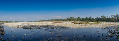 Panoramic view of Murti river, riverbed in foreground with flowing water and stones. Scenic beauty of Dooars landscape, West Bengal, India 스톡 콘텐츠