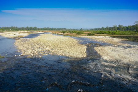 Murti river, riverbed in foreground with flowing water and stones. Scenic beauty of Dooars landscape, West Bengal, India 스톡 콘텐츠