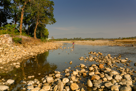 Murti river in the morning, riverbed in foreground with flowing water and stones. Scenic beauty of Dooars landscape, West Bengal, India