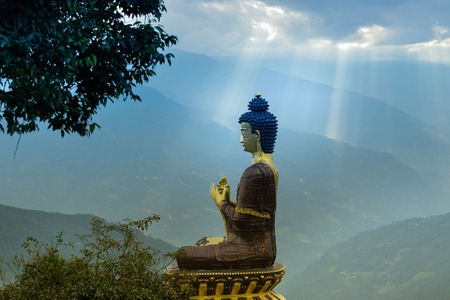Sunrays falling on Beautiful huge statue of Lord Buddha, at Rabangla , Sikkim , India. Surrounded by Himalayan Mountains. It is called Buddha Park - a popular tourist attraction.
