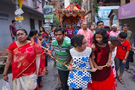 HOWRAH, WEST BENGAL , INDIA - JULY 22TH 2018 : Young Bengali Hindu devotees dragging Holy rope to pull Rath, chariot, of God Jagannath, Balaram and Goddess Suvadra as ritual , on the street.