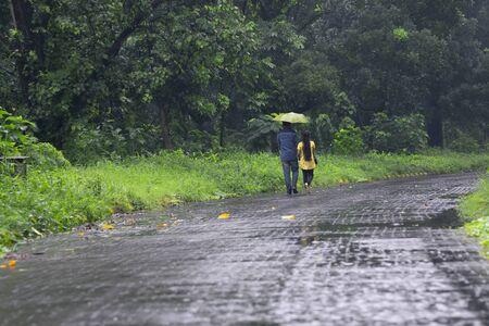 Couple romantique avec un parapluie marchant et disparu dans la nature, image conceptuelle de la saison des pluies, Kolkata, Bengale occidental. Mousson de l'Inde. Banque d'images