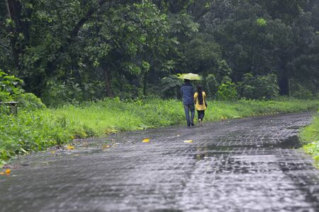 Romantic couple with one umbrella walking and faded away in nature, conceptual stock image of rainy season, Kolkata, West Bengal. Monsoon of India. Stock Photo