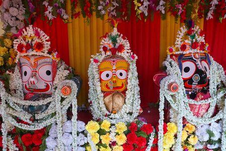 Idols of God Jagannath, Balaram and Goddess Suvadra. Lord Jagannath is being worshipped with garlands for Rath jatra festival - at Howrah, West Bengal, India. Stock Photo