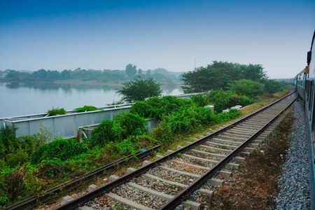 A train passing beside backwaters of Kerala, India - The Kerala backwaters are a network of brackish lagoons and lakes lying parallel to the Arabian Sea coast southern India. Blue sky background.