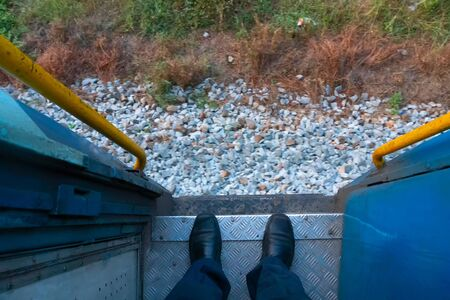 A pair of shoes of a passenger on the front gate of a railway coach while the train is passing through railway tracks. Huge passengers are carried across the country by coaches and helps travellers. Stock Photo