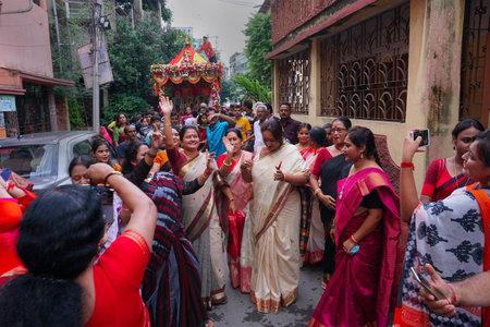 Howrah, West Bengal , India - July 22nd 2018 : Bengali Hindu sari clad devotee ladies dancing in joy, in front of Rath, chariot, of God Jagannath, Balaram and Goddess Suvadra as ritual on the street.