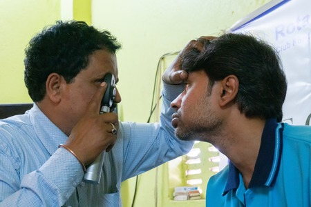 Kolkata, West Bengal, India - February 25th, 2018 : Male Doctor eye specialist checking eye sight of young man , at a free public eye testing camp. Editorial stock image.