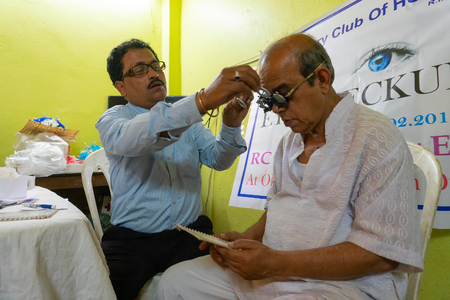 Kolkata, West Bengal, India - February 25th, 2018 : Male Doctor eye specialist checking eye sight of old man , at a free public eye testing camp. Editorial stock image.