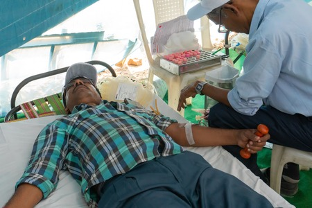 Kolkata, West Bengal, India - February 25th, 2018 : Male medical person collecting blood from young male volunteer lying on bed inside public blood donation camp. Editorial stock image.