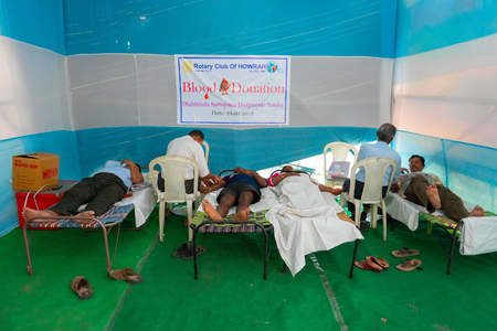 Kolkata, West Bengal, India - February 25th, 2018 : Male medical persons collecting blood from young male and female volunteers lying on bed inside public blood donation camp. Editorial stock image.