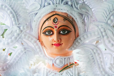 Kolkata, West Bengal, India - 7th October 2018 : Clay idol face of Goddess Durga, with white dress for Durga Puja festival. Biggest festival of Hinduism, celebrated all over the world.