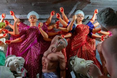 Kolkata, West Bengal, India - 7th October 2018 : Clay idols of Goddess Durga, dresses is sari - a traditional bengali dress - being prepared for