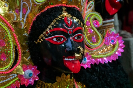 Kolkata, West Bengal, India - 7th October 2018: Painted idol of Goddess Kali with black face and red tongue. Goddess of Time, Creation, Destruction and Power. Beautifully decorated with shining crown.