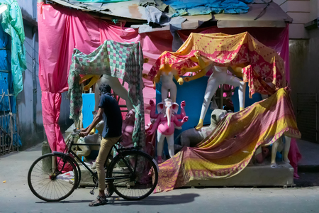Kolkata, West Bengal, India - 7th October 2018: A cyclist watching painted clay idol of Goddess Durga and her family covered by Sari- a traditional Indian dress. Preparation for