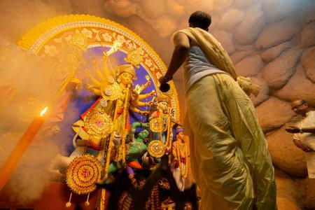 Kolkata, India - October 16, 2018 : Young Hindu Priest worshipping Goddess Durga under holy smoke, Durga Puja festival ritual. - shot at night under colored light and Holy smoke. Durga Puja festival. Editorial