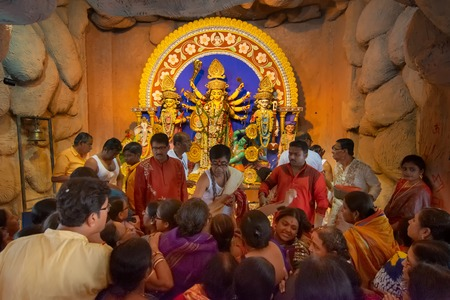 Kolkata, India - October 16, 2018 : Devotees offering flowers and praying to Goddess Durga, called Pushpanjali, as a ritual to Durga Puja festival celebration. It is the biggest festival of Hinduism.