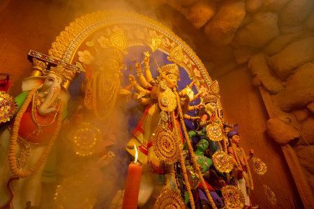Kolkata, India - October 16, 2018 : Goddess Durga idol under holy smoke, Durga Puja festival ritual. - shot at night under colored light. Festival of Hinduism.