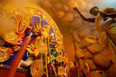 Kolkata, India - October 16, 2018 : Young Hindu Priest worshipping Goddess Durga with sacred lamp under holy smoke, aarti - sacred Durga Puja festival ritual. - shot at night under colored light. Editorial