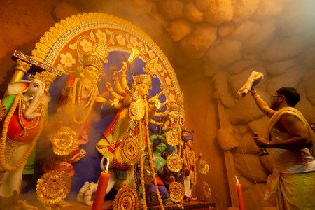 Kolkata, India - October 16, 2018 : Hindu Priest worshipping Goddess Durga with sari, Indian womans dress material under holy smoke, Durga aarati - Puja festival ritual. - shot under colored light. Editorial