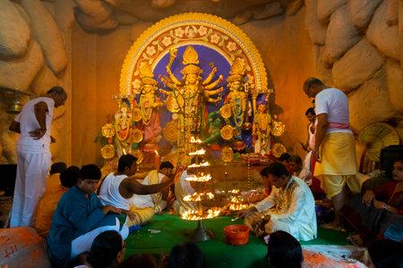 Kolkata, India - October 16, 2018 : Priest lighting up 108 lamps during Sandhi Puja, the sacred juncture of Ashtami, eighth day and Nabami, nineth day, as Hindu ritual for praying to Goddess Durga.