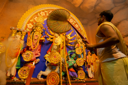 Kolkata, India - October 16, 2018 : Young Hindu Priest worshipping Goddess Durga and airing her idol with a big fan, Durga Puja festival ritual. - shot under colored light. Festival of Hinduism.