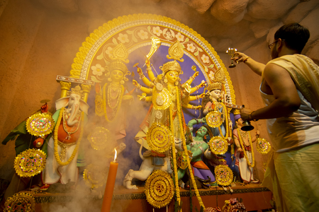 Kolkata, India - October 16, 2018 : Young Hindu Priest worshipping Goddess Durga with sacred lamps under holy smoke, Durga aarati - sacred Durga Puja ritual - shot at night under colored light. Editorial