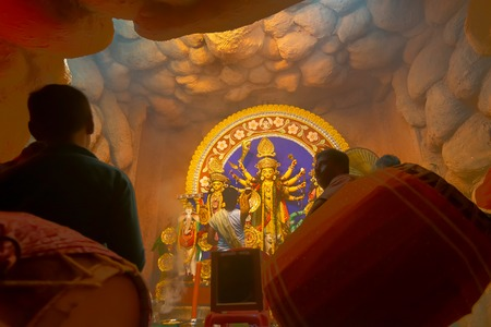 Kolkata, India - October 16, 2018 : Young Hindu Priest worshipping Goddess Durga under holy smoke with dhaakis (drummers) performing. Durga Puja - shot at night under colored light .