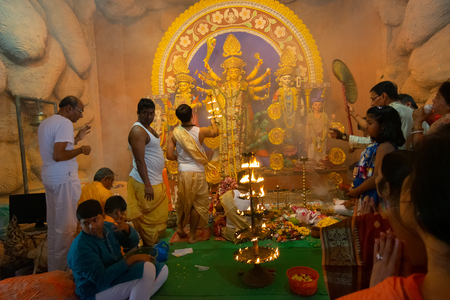 Kolkata, India - October 16, 2018 : Hindu priest praying to Goddess Durga with 108 lamps lit during Sandhi Puja, the sacred juncture of time of Ashtami, eighth day and Nabami, nineth day as ritual. Editorial