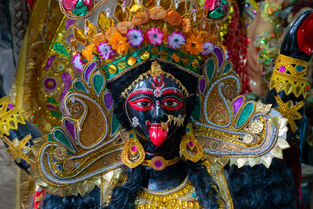 Kolkata, West Bengal, India - 7th October 2018 : Clay idol of Goddess Kali with black face and red tongue. Goddess of Time, Creation, Destruction and Power. Beautifully decorated with shining crown.