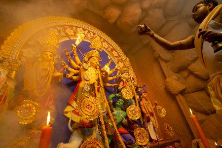 Kolkata, India - October 16, 2018 : Young Hindu Priest worshipping Goddess Durga with comch shell under holy smoke, Durga Puja festival ritual. - shot at night under colored light. Hindu Festival.