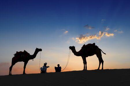 Silhouette de deux chameliers et leurs chameaux dans les dunes de sable du désert de Thar, Rajasthan, Inde. Coucher de soleil avec un ciel bleu en arrière-plan. Les chameliers vivent de la randonnée à dos de chameau des touristes. Banque d'images