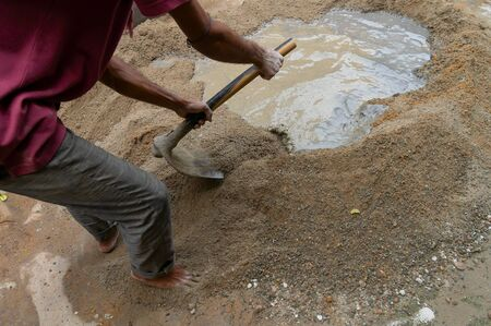 Indian labour mixing cement and water manually on floor using a shovel. Stock image.