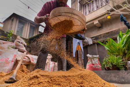 Howrah, West Bengal, India - 6th January 2020 : Indian labour separating sand and gravel manually using a sieve, for using the sand for cementing work, Image shot from low angle.