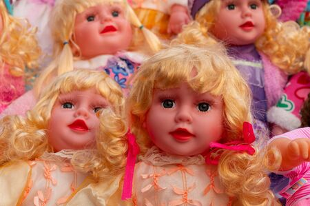 Colourful tiny blonde baby dolls for sale at retail shop at Christmas market, New Market area, Kolkata, West Bengal, India.