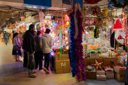 Kolkata, West Bengal, India - 29th December 2019 : Buyers chekcing out goods from Illuminated shop, New Market at esplanade area in the evening. It is one of the oldest and busiest markets in Kolkata.