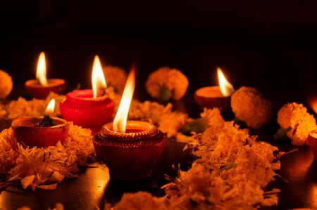 Very low angle view of Rangoli flowers and candles or diyas, Deepawali lights at night. Dark background stock image. Stock Photo