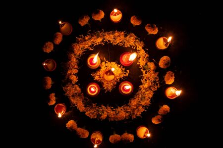 Top view of Rangoli flowers put in circle and candles or diyas placed around them, Deepawali lights at night. Dark background stock image.