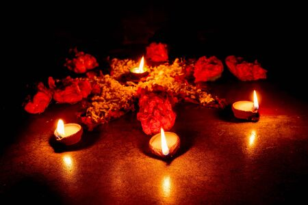 Low angle Rangoli flowers and candles or diyas, Diwali lights at night. Dark background stock image.