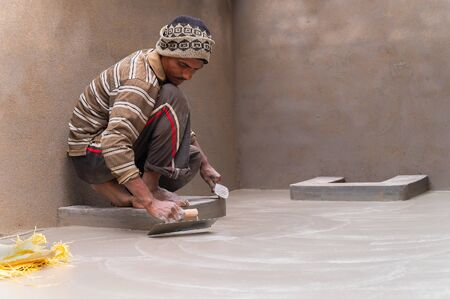 Howrah, West Bengal, India - 6th January 2020 : Indian labour levelling plastered floor using flat trowel and cement manually, In seated position. Stock image.