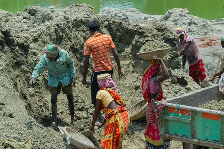 Howrah, West Bengal, India - 7th May 2017 : Indian male and female workers digging and carrying out soil at buliding construction site. India has a huge population of daily wage earners.