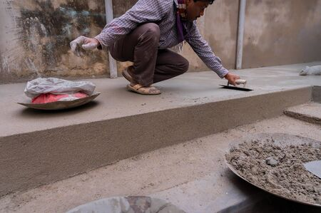 Howrah, West Bengal, India - 6th January 2020 : Indian labour levelling plastered floor using flat trowel and cement manually, Stock image.