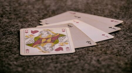 closeup scene of a hand of poker, playing cards opened on the table in a game, poker, four of a kind and queen .