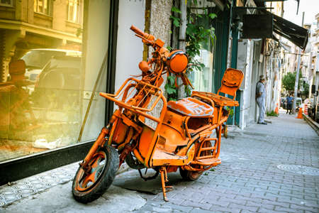 an almost scrapped modified scooter, retro city bike, painted all orange, phosphorous, stays as an offbeat object on the street.