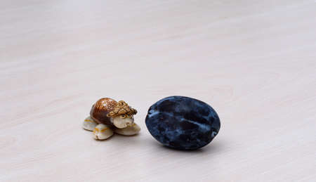 a small tortoise trinket, a decorative object, with a black plum in front.