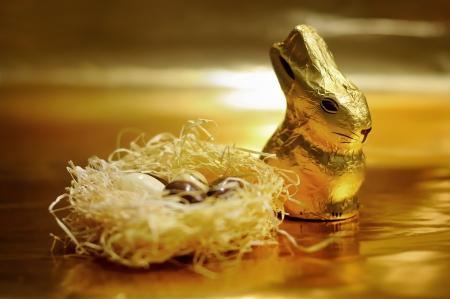 Pasen chocolade konijn en eieren op gouden achtergrond Stockfoto
