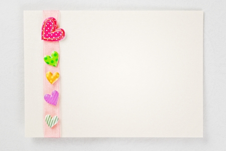 Blank card with colorful hearts over rose ribbon photo